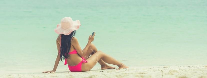 the beautiful girl listen music on the beach